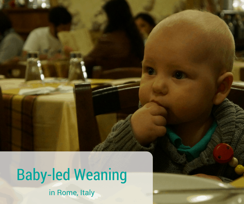 baby eating food in Rome in a high chair at a restaurant.