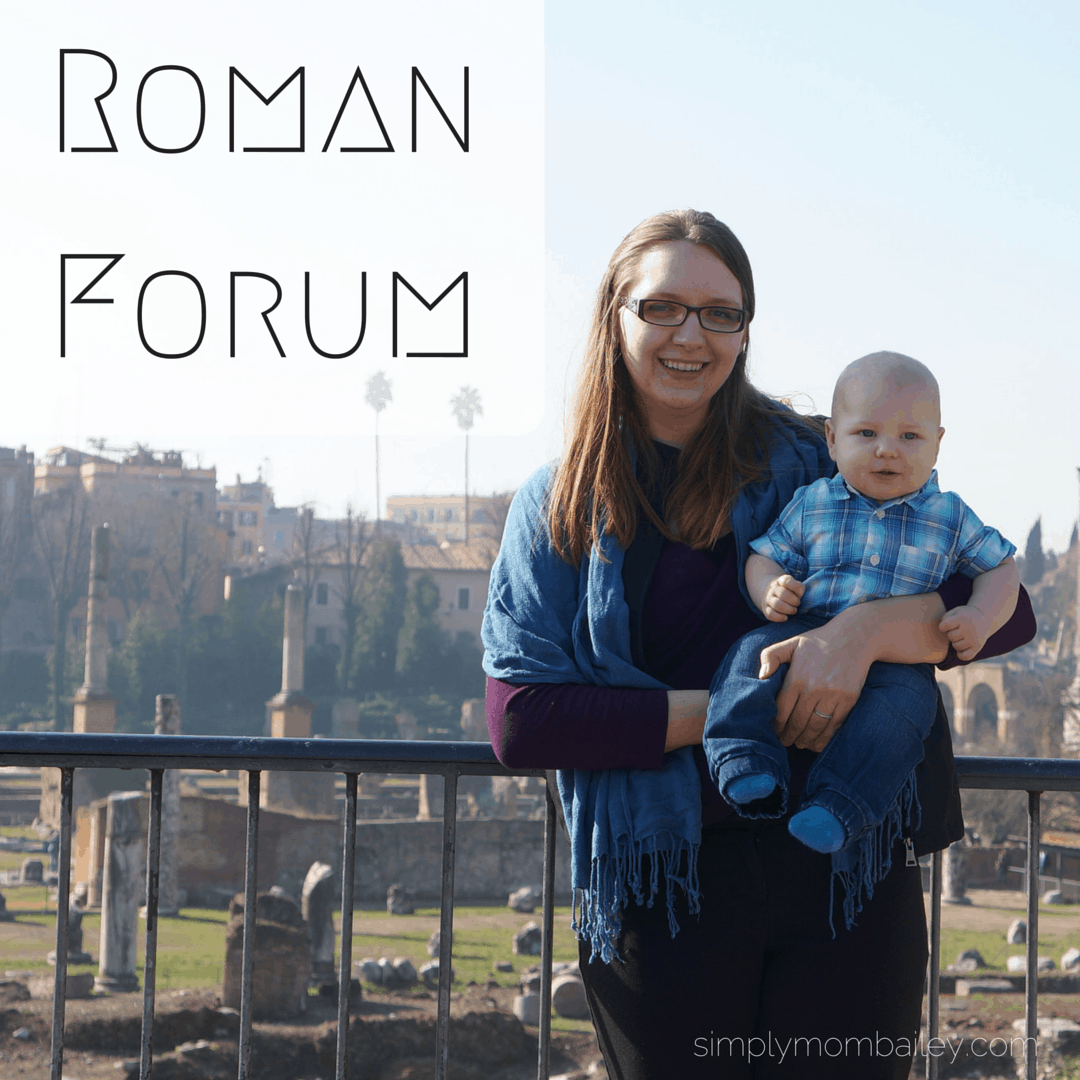 mom holding baby with forum in background in Rome, Italy