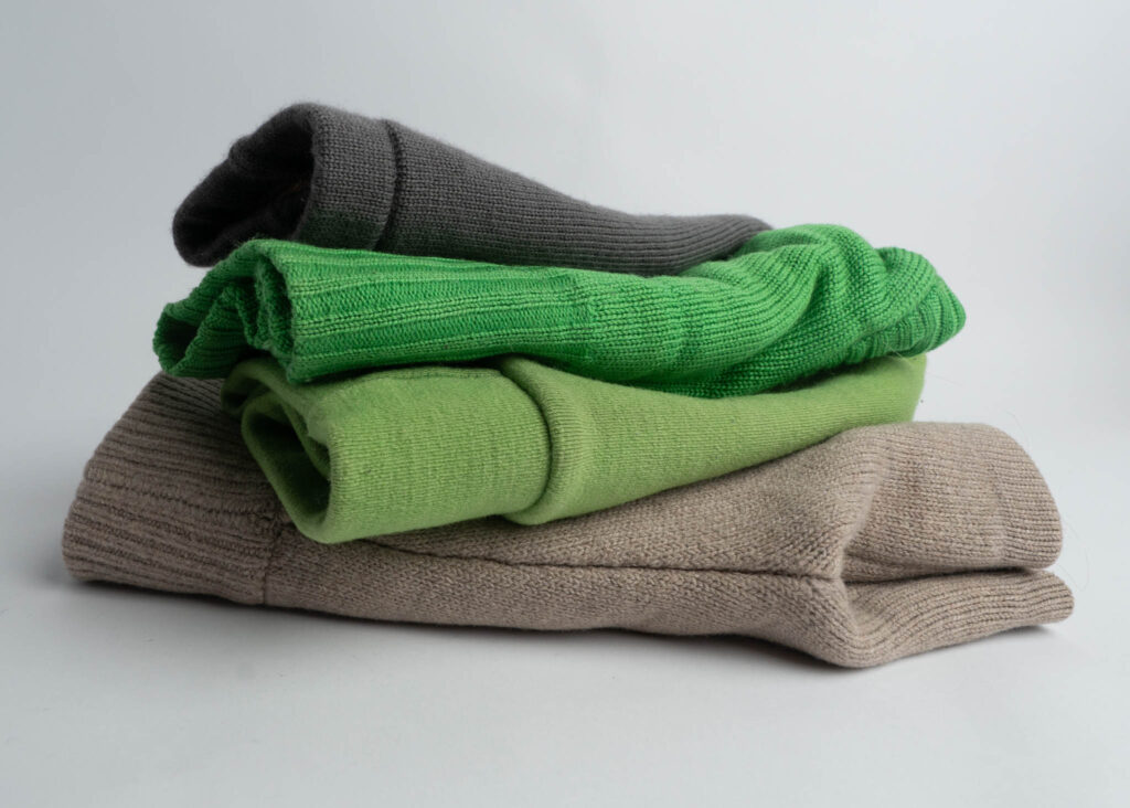 Image of wool diaper covers folded in half and stacked on top of each other: features Sloomb Shorties, HumBird Interlock Cover in Green, Imagine Baby Wool Cover in Green, and Sloomb Underwoolies in Grey.