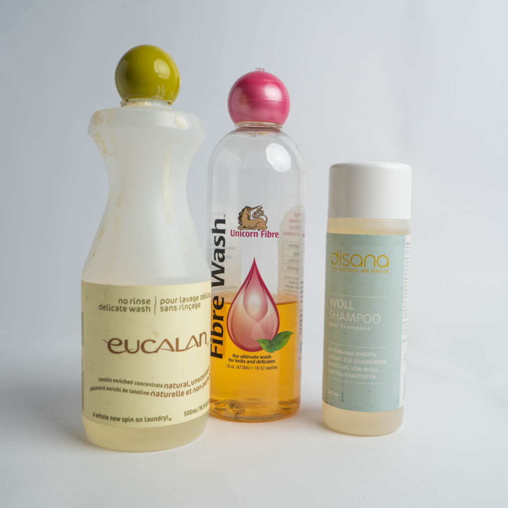 An Image featuring three different types of wool wash recommended for washing wool cloth diapers. From left to right: 16oz bottle of Euclan, 16oz bottle of Unicorn Fibre Wash, and a bottle of Disana Wool Wash